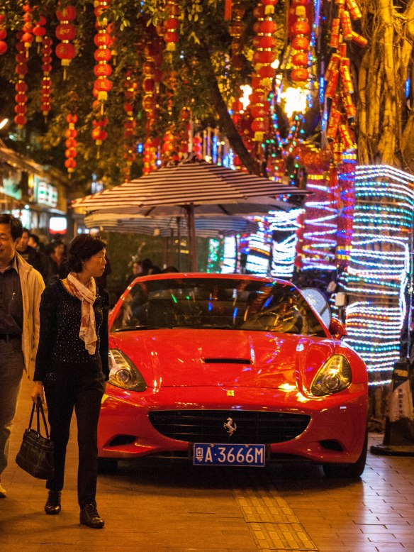 Ferrari parked  on the sidewalk in front of a high end seafood restaurant in Guangzhou.
