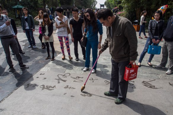 This gentleman was practicing calligraphy on the sidewalk using water for ink. He was writing poetry of course.
